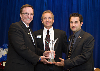 2015 AAR President Jim Sexton presents the Community Outreach Award in the Association category to Phil Annett and Aaron Pfeifer representing the Lake Havasu Association of REALTORS®