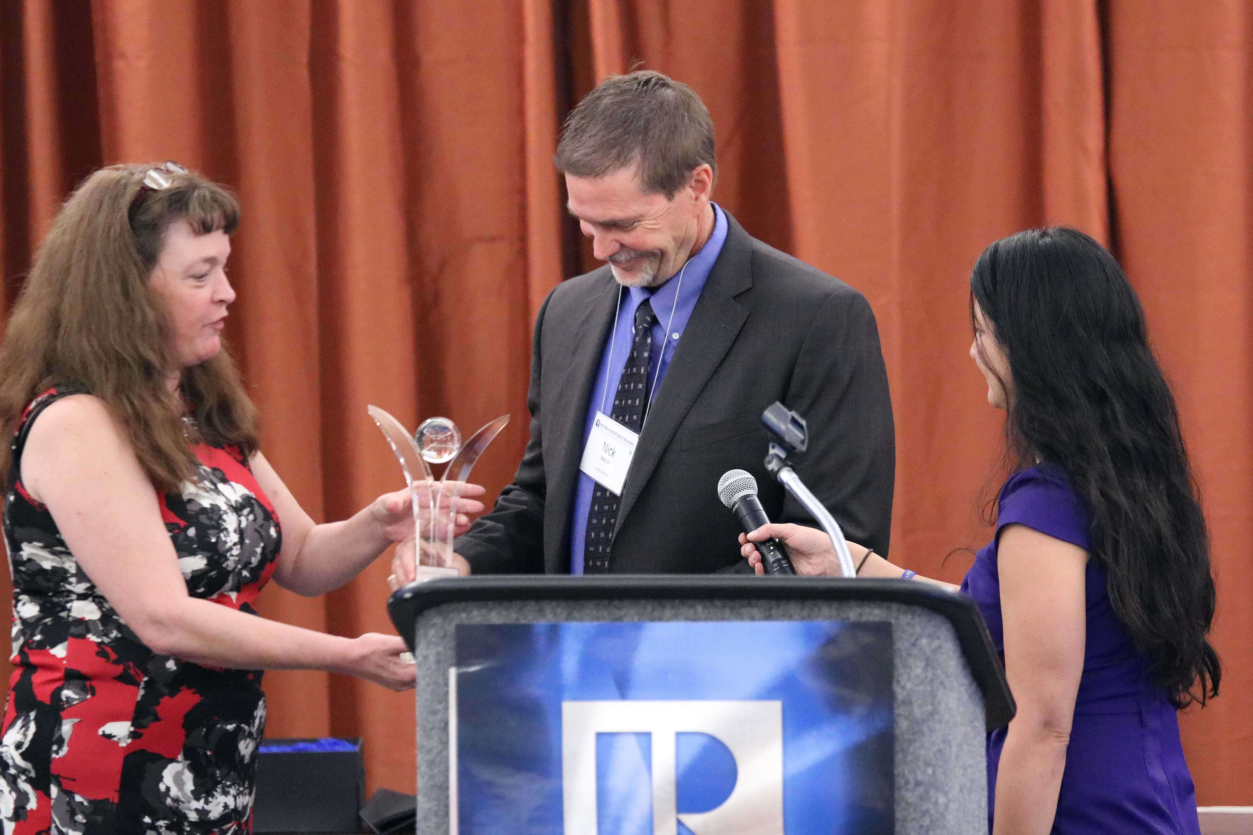 Arizona REALTORS® Director of Association Relations Monica Schulik and 2017 President Paula Monthofer presents the Community Outreach REALTOR® Award to Nick Bastian.